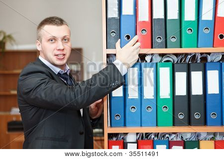 Handsome Male Business Executive Standing Behind A Bookstand