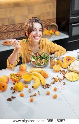 Portrait Of A Young Cheerful Woman Eating Salad At The Table Full Of Healthy Raw Vegetables And Frui