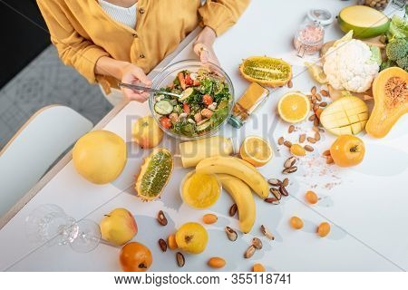 Woman Eating Salad At The Table Full Of Healthy Raw Vegetables And Fruits, Cropped View From Above W