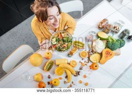 Cheerful Woman Eating Salad At The Table Full Of Healthy Raw Vegetables And Fruits On The Kitchen At