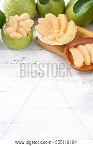 Fresh Peeled Pomelo, Pummelo, Grapefruit, Shaddock On Bright Wooden Table Background. Seasonal Fruit