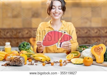 Woman Holding Human Liver Model With Variety Of Healthy Fresh Food On The Table. Concept Of Balanced