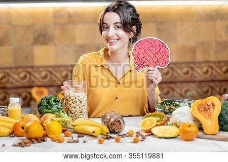 Woman Holding Human Brain Model With Variety Of Healthy Fresh Food On The Table. Concept Of Balanced