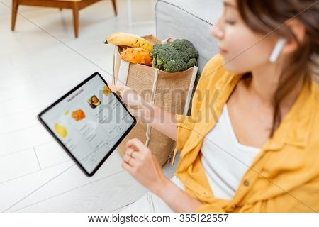 Young Woman Shopping Online Using A Digital Tablet, Sitting With Bag Full Of Products At Home. Conce