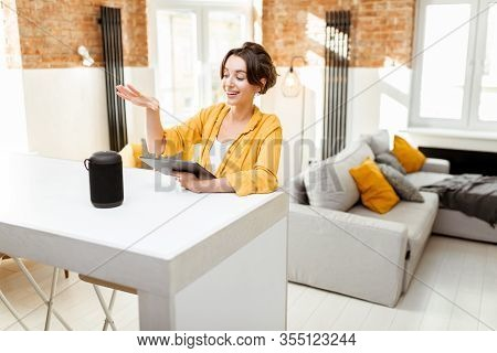 Happy Young Woman Controlling Smart Home Devices With A Voice Commands And Smart Speaker At Home. Co