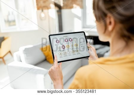 Controlling Smart Home Devices Using A Digital Tablet With Launched Application. Smart Home Concept