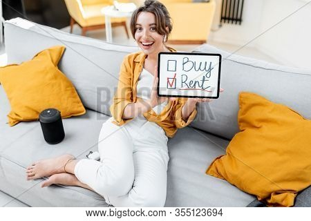Young Woman Decides Between Buying Or Renting Real Estate, Holding Digital Tablet Indoors. Concept O