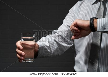 Businessman closeup portrait, he standing and posing with glass of water, looking at wrist watch, dark wall background