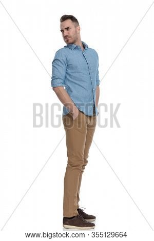 Side view of bothered casual man frowning and looking over shoulder while wearing blue shirt, standing on white studio background