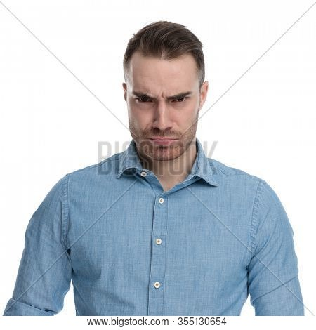 Bothered casual man looking forward and frowning while wearing blue shirt, standing on white studio background