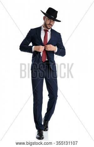 Tough businessman unbuttoning his jacket while wearing hat and suit, stepping on white studio background