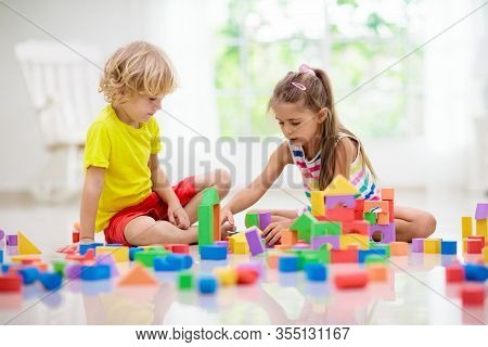 Kids Play With Colorful Blocks. Little Boy And Girl Build Tower At Home Or Day Care. Educational Toy