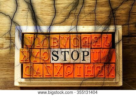 Stop - Isolated Abstract In Wood Type Stamps And Black Lightning Or Thunder Against Wooden Backgroun