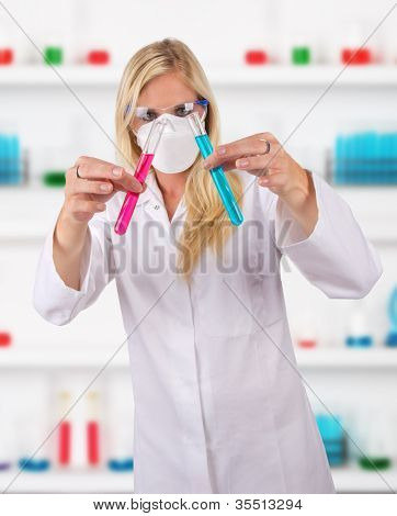 Young attractive laboratory assistant researching test tubes