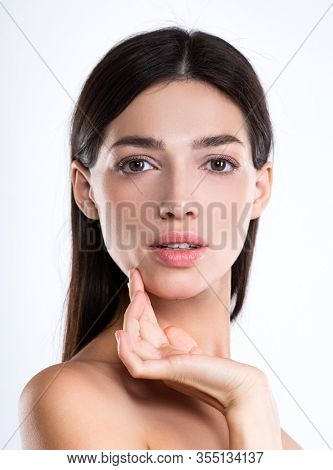 Portrait of beautiful young brunette woman with clean face. Beautiful face of young adult woman with clean fresh skin - isolated on white. Front portrait of woman with beauty face. 