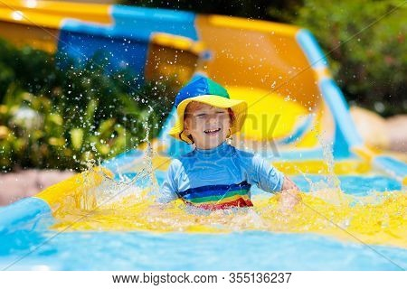 Kids On Water Slide In Aqua Park. Summer Vacation