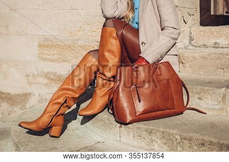 Close Up Of Woman Wearing Stylish Orange Boots Leather Skirt Holding Purse Outdoors. Spring Fashion