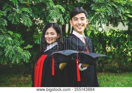 A Man And Woman Couple Dressed In Black Graduation Gown Or Graduates With Congratulations With Gradu