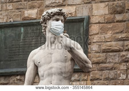 The Statue Of David in the Piazza della Signoria In Italy Wearing a Protective Face Mask.