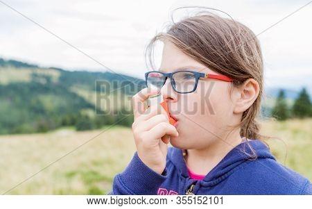 Girl Having Asthma Using Asthma Inhaler Outdoors - Shallow Depth Of Field