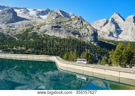 Fedaia Lake, Italy - August 27, 2019: Bus On The Fedaia Lake Dam, Reflected In The Turquoise Waters,