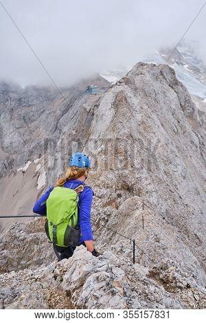 Woman On Via Ferrata Eterna Brigata Cadore, Ascending The Eastern Summit Of The Marmolada Ridge Line