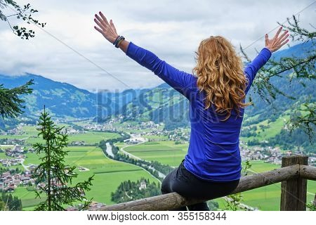 Happy Woman With Arms Spread Out In Joy And Curly Hair Looks Towards Zillertal Valley In Austria, Fr