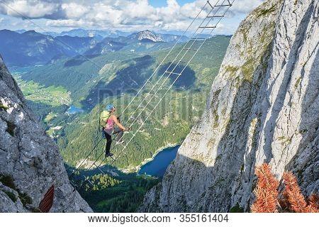 Woman On Via Ferrata Ladder Above Gosau Lake, On The Intersport Klettersteig Donnerkogel Route, In A