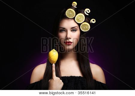 Portrait of beautiful brunnete with lemons in her hairstyle