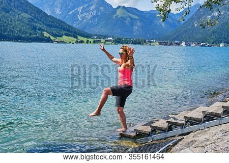 Lady Tourist Balancing On One Foot At The Edge Of Achen Lake (achensee), Tirol, Austria, On A Bright
