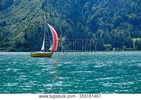 Boat With Colorful Sails At Achen Lake (achensee), Tirol, Austria, With Turquoise Waters.