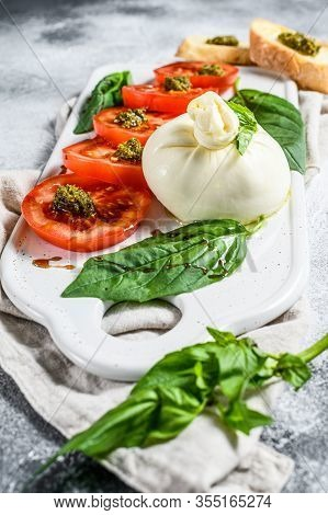 Burrata Cheese Salad Including Sliced Tomato, Basil Leaves With Pesto. Gray Background. Top View