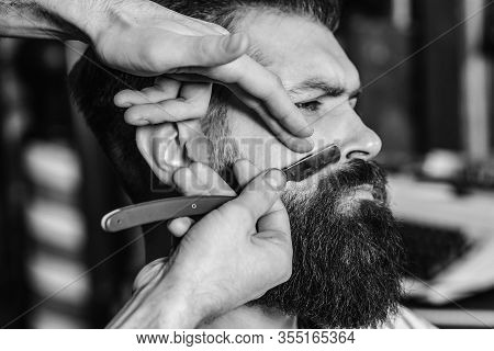 Barber With Straight Razor Shaving Bearded Man. Hairstylist Serving Client. Barber Shop. Confident B