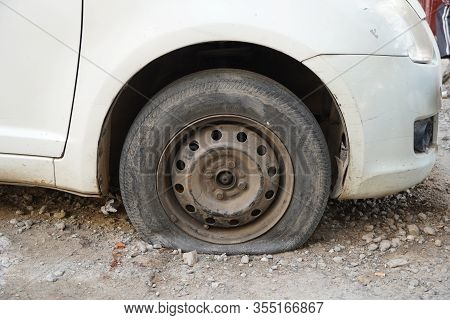 Tire Leak, Close Up Wheel Of Old White Vintage Car. Car Wheel Flat Tire On The Road. Deflated The Ty