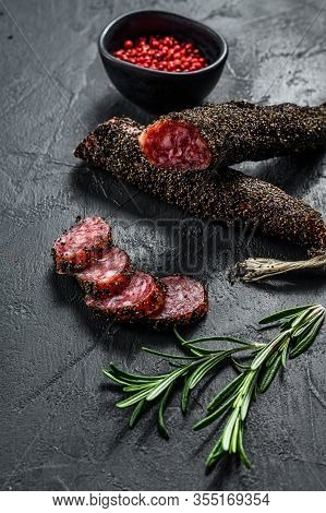 Wurst, Fuet, Sliced Sausage. Pork Sausage. Black Background. Top View