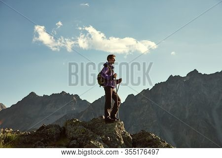Climber On Trail In The Mountains. A Man With A Backpack In A Hike.