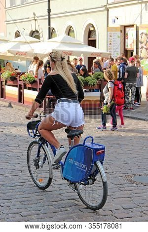 Warsaw / Poland. 27 July 2019: Young Girl In White Shorts Rides Bicycle. Sexy Girl Rides Bicycle Aro