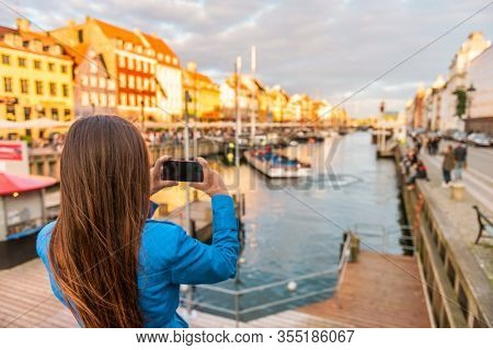 Copenhagen Denmark travel tourist woman taking photo of Nyhavn water canal old town famous tourism destination, attraction in scandinavia, Europe.