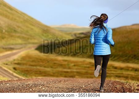 Running woman on trail run doing fitness exercise in spring autumn mountains. Person training outside in cold weather in blue sportswear.