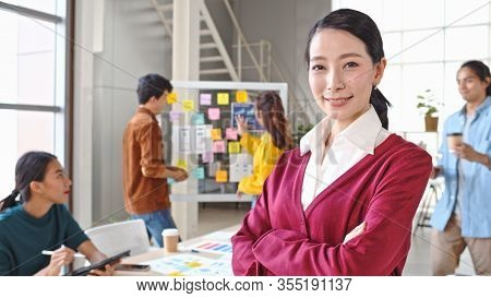 Portrait Of Beautiful Asian Woman Smiling, Arms Crossed In Modern Office, With Young Creative Team W