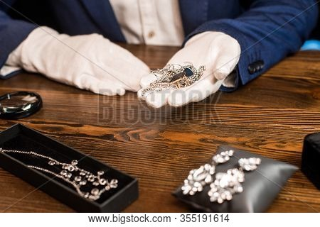 Cropped View Of Jewelry Appraiser Holding Jewelry Near Magnifying Glass On Table On Black Background