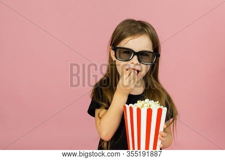 Cute Little Girl Eats Popcorn From Striped Packaging And Watches A Movie With 3d Glasses. Cinema Adv
