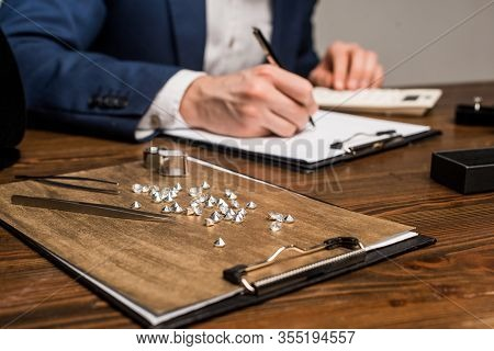 Selective Focus Of Gemstones And Tools Near Jewelry Appraiser Writing On Clipboard On Table Isolated