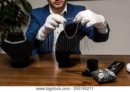 Cropped View Of Jewelry Appraiser In Gloves Holding Necklace Near Jewelry On Table In Workshop