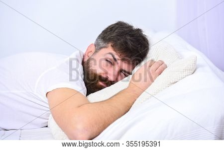 Man In Shirt Laying On Bed, White Wall On Background. Macho With Beard And Mustache Sleeping, Relaxi