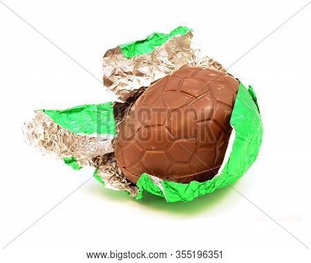 An Isolated Over White Image Of A Hollow Chocolate Egg Being Unwrapped From Its Green Foil.