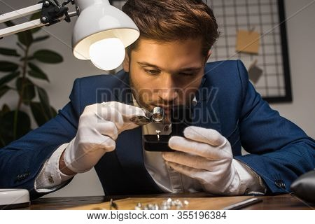 Handsome Jewelry Appraiser Examining Ring With Gemstone In Box Near Lamp On Table
