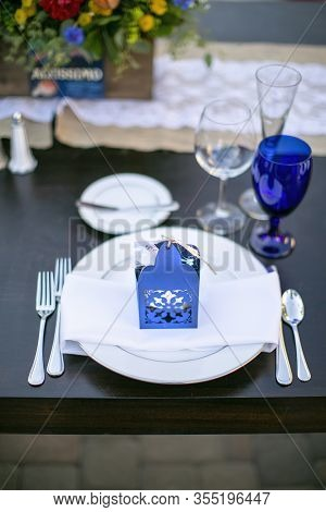 Table Set For A Patio Wedding Decorated With Orange And Yellow Flower, Blue And Crystal Wind Glasses