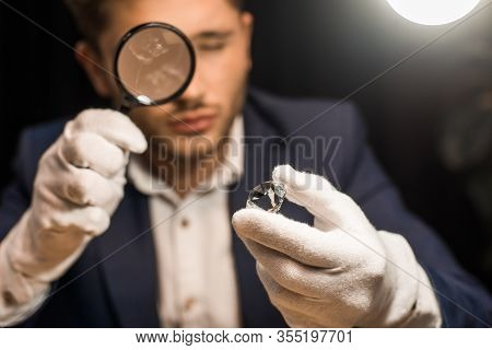 Selective Focus Of Jewelry Appraiser Examining Gemstone With Magnifying Glass On Black Background