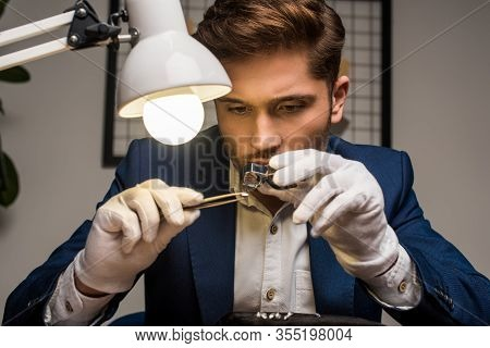 Handsome Jewelry Appraiser Working With Gemstone In Tweezers And Magnifying Glass At Table In Worksh